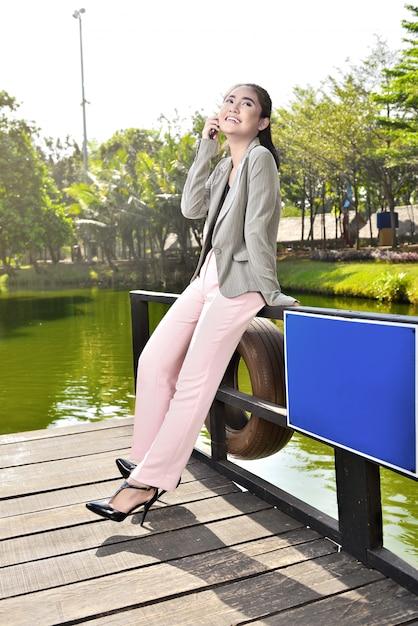 Femme d'affaires asiatique souriante parlant au téléphone tout en vous relaxant Photo Premium
