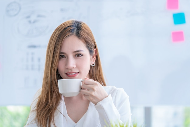 Femme d'affaires asiatique vérifie le rapport en buvant du café Photo Premium