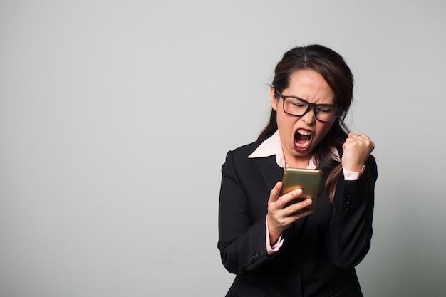 Femme d'affaires asiatiques à l'aide d'un téléphone intelligent. déception et action hurlante. Photo Premium
