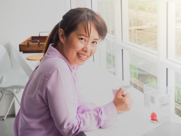 Femme d'affaires asiatiques tenant un verre de café au café avec spectacle de poisson. Photo Premium