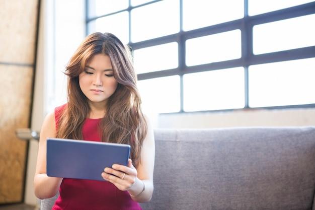 Femme d'affaires assis sur un canapé et à l'aide de tablette numérique au bureau Photo Premium