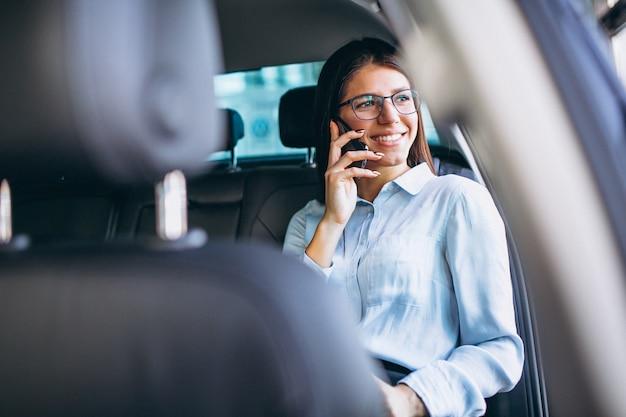 Femme d'affaires assis dans la voiture et à l'aide de téléphone Photo gratuit