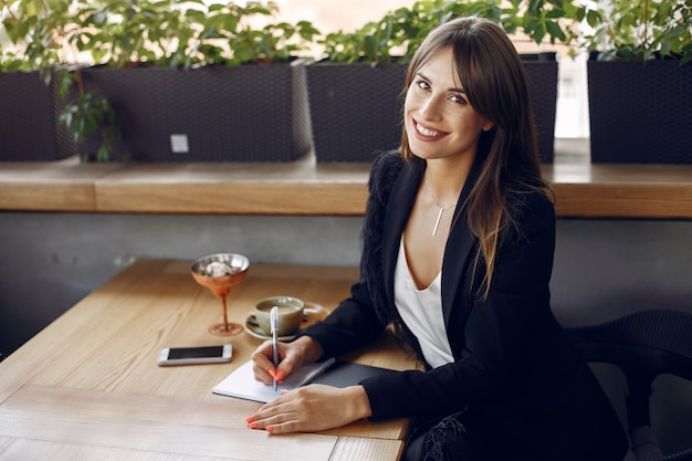 Femme d'affaires assis à la table dans un café et travaillant Photo gratuit