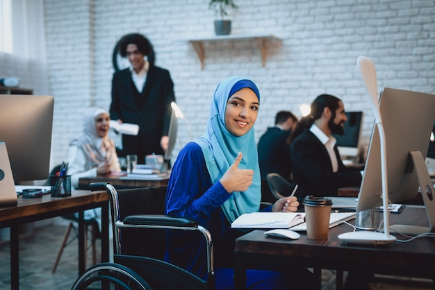 Femme d'affaires attrayant en hijab au poste de travail. Photo Premium
