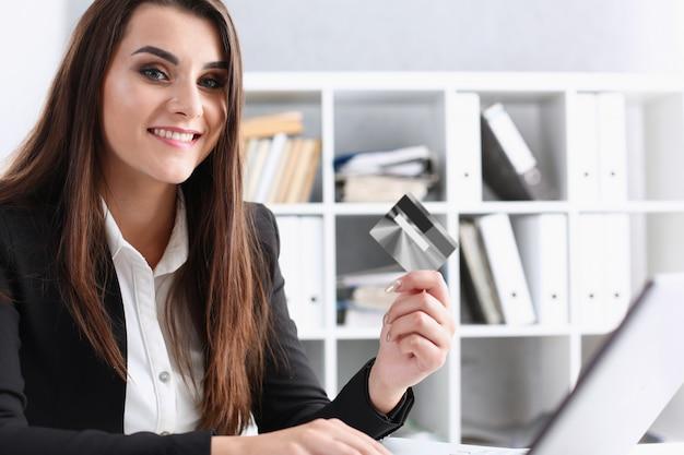 Femme D'affaires Au Bureau Est Titulaire D'une Carte De Débit En Plastique Dans Sa Main Photo Premium