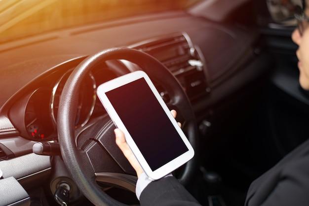 Femme d'affaires au volant et à l'aide d'une tablette, concept de technologie de communication Photo Premium