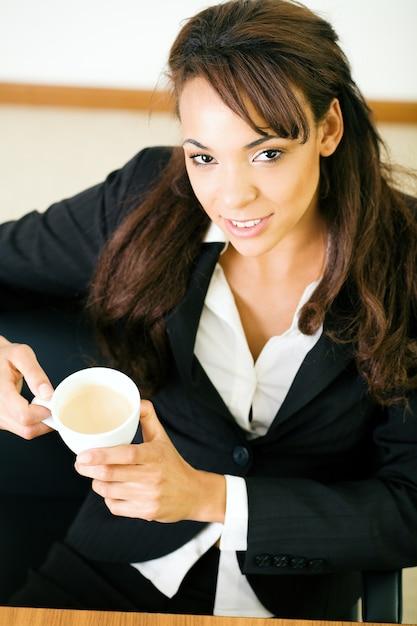 Femme d'affaires ayant un double expresso Photo Premium