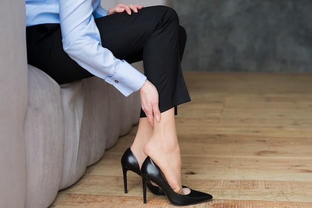 Femme d'affaires ayant des douleurs dans les jambes Photo gratuit