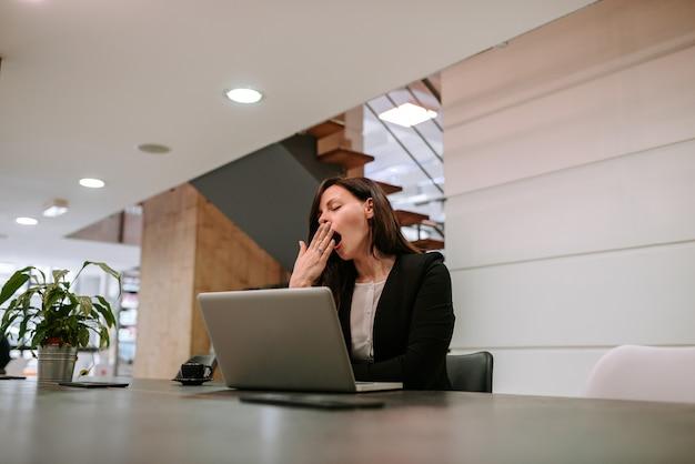 Femme d'affaires bâillant sur le lieu de travail. Photo Premium