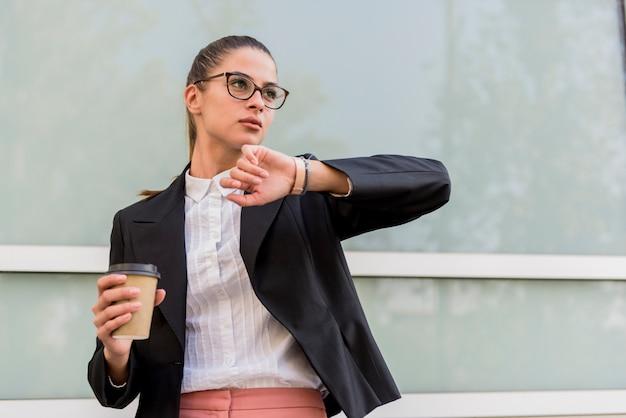 Femme affaires, bâtiment, regarder, montre-bracelet, et, boissons, café Photo Premium