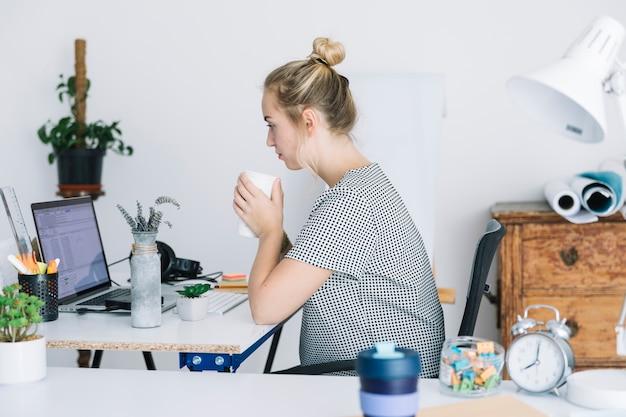 Femme d'affaires, boire du café tout en travaillant dans le bureau Photo gratuit