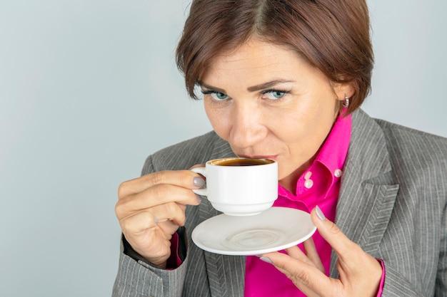 Femme D'affaires Boit Du Café D'un Gros Plan De Tasse Blanche Photo Premium