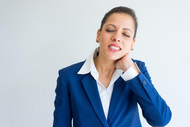 Femme d'affaires bouleversée avec douleur au cou Photo gratuit