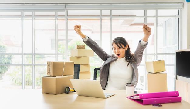 Femme d'affaires bras avec ordinateur portable et une boîte en carton Photo Premium