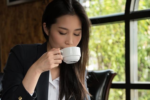 Femme d'affaires buvant une tasse de café le matin à la boutique. Photo Premium