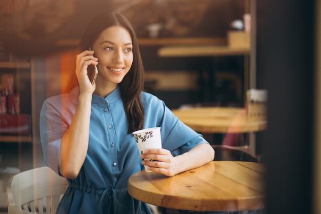 Femme d'affaires avec café et parler au téléphone dans un café Photo gratuit