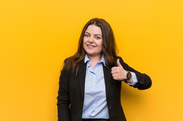 Femme d'affaires caucasien de taille plus jeune souriant et levant le pouce Photo Premium