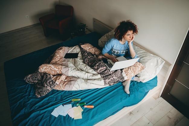 Femme D'affaires Caucasienne Réfléchie Aux Cheveux Bouclés Assis Sur Le Canapé Avec Un Ordinateur Portable En Prenant Quelques Notes Dans Le Livre Photo Premium