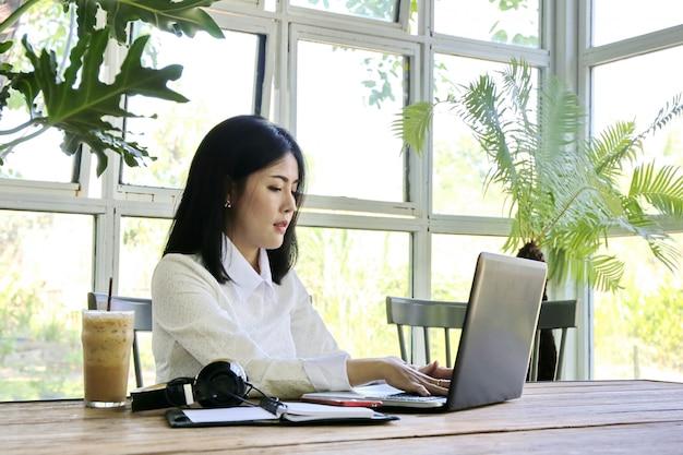 Femme d'affaires, charmante peau beige belle entreprise asiatique femme chic main travailler sur ordinateur portable dans la maison de verre. Photo Premium