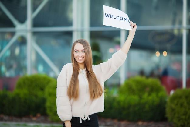 Femme affaires, à, cheveux longs, tenue, signe, conseil, accueil, aéroport Photo Premium