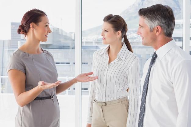 Femme d'affaires en conversation avec ses collègues Photo Premium