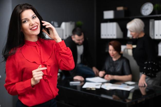 Femme affaires, conversation, téléphone, sur, employés bureau, discuter, projet Photo Premium
