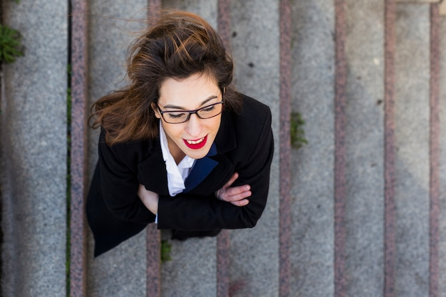 Femme d'affaires en costume debout dans les escaliers à l'extérieur Photo gratuit