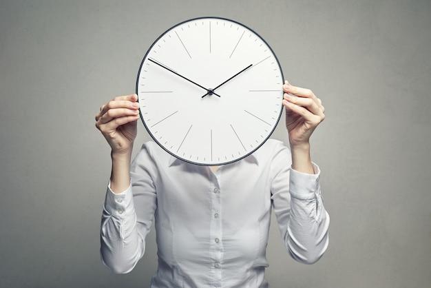 Femme d'affaires couvrant son visage avec une horloge Photo Premium