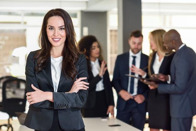 Femme D'affaires Dans Un Bureau Moderne Avec Des Hommes D'affaires Travaillant Photo gratuit