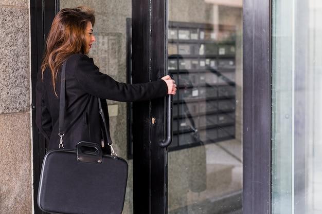 Femme d'affaires dans des vêtements noirs entrant dans le bâtiment Photo gratuit