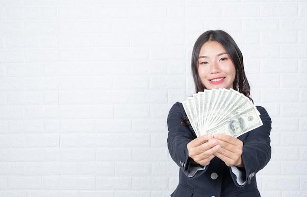 Femme d'affaires détenant des billets de banque, espèces séparément, mur de briques blanches fait des gestes avec la langue des signes. Photo gratuit