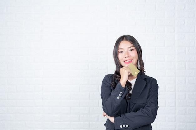 Femme d'affaires détenant une carte de paiement séparée, mur de briques blanches fait des gestes avec la langue des signes. Photo gratuit