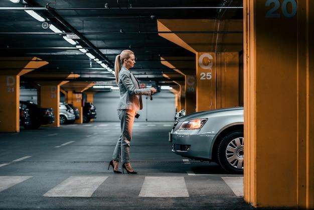 Femme D'affaires élégant Avec Des Clés De Voiture Devant Une Voiture Dans Un Parking Souterrain. Photo Premium