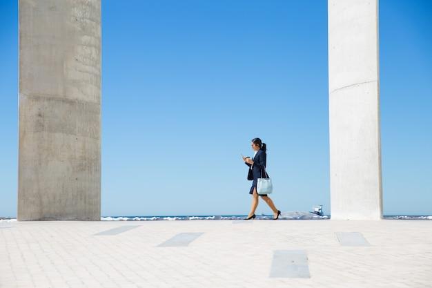 Femme d'affaires élégante marchant le long de la promenade Photo gratuit