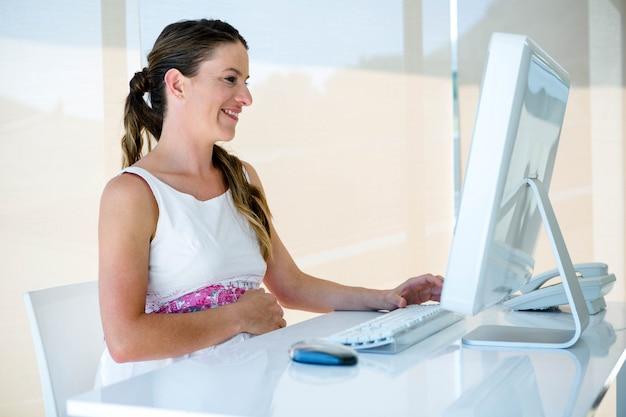 Femme D'affaires Enceinte Souriante Dans Son Bureau, à Son Bureau Photo Premium