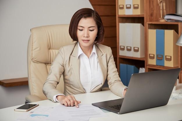 Femme d'affaires ethnique travaillant avec du papier Photo gratuit
