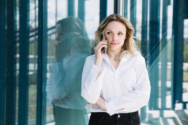 Femme d'affaires faisant un appel téléphonique à côté de windows Photo gratuit