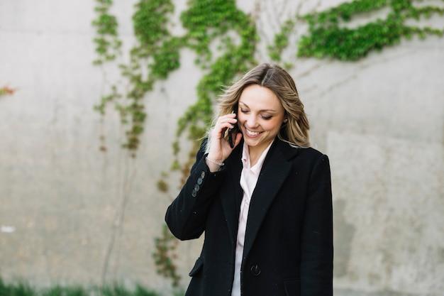 Femme d'affaires faisant un appel téléphonique à l'extérieur Photo gratuit