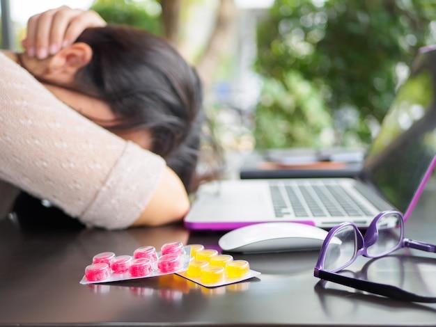 Femme d'affaires fatigué a mal à la tête du syndrome de bureau après de longues heures de travail sur ordinateur. Photo Premium