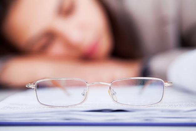 Femme d'affaires fatiguée et surmenée dormant au travail Photo Premium