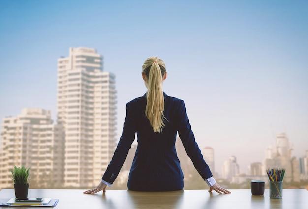 Femme d'affaires féminine regarde par la fenêtre pour réussir Photo Premium