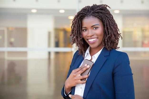 Femme d'affaires gaie avec une cellule qui reçoit de bonnes nouvelles Photo gratuit