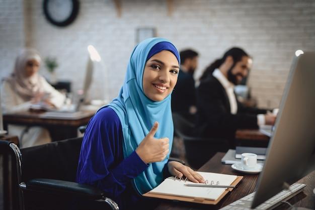 Femme d'affaires handicapée en hijab avec le pouce Photo Premium