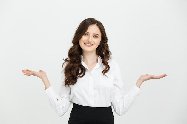Femme d'affaires heureuse et surprise montrant le produit. Photo Premium