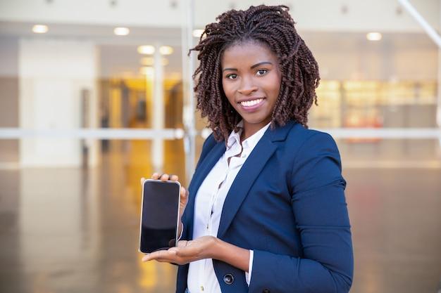 Femme d'affaires heureux présentant sur l'écran de la cellule Photo gratuit