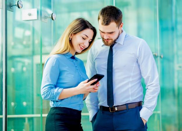 Femme d'affaires et homme d'affaires avec mobilephon planant un travail Photo Premium