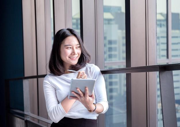 Femme d'affaires jeune heureux et réussi sourire avec le résultat dans la tablette numérique Photo Premium