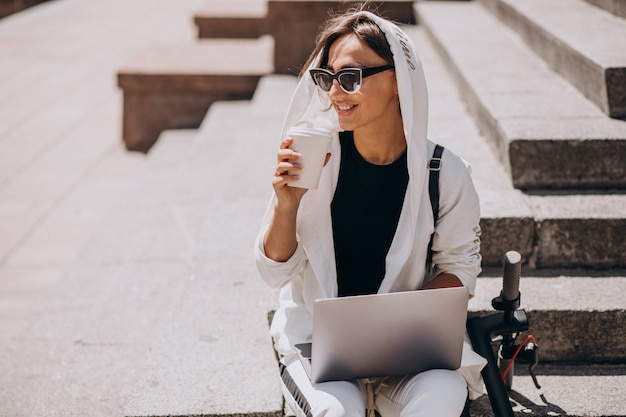 Femme d'affaires jeune avec ordinateur portable assis dans les escaliers avec scooter Photo gratuit