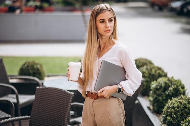 Femme d'affaires jeune avec ordinateur portable, boire du café en dehors du café Photo gratuit