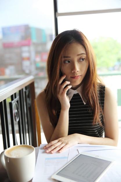 Femme d'affaires jeune avec smartphone et café Photo Premium